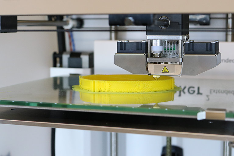 The fabrication lab 3D printer prints out a yellow material.