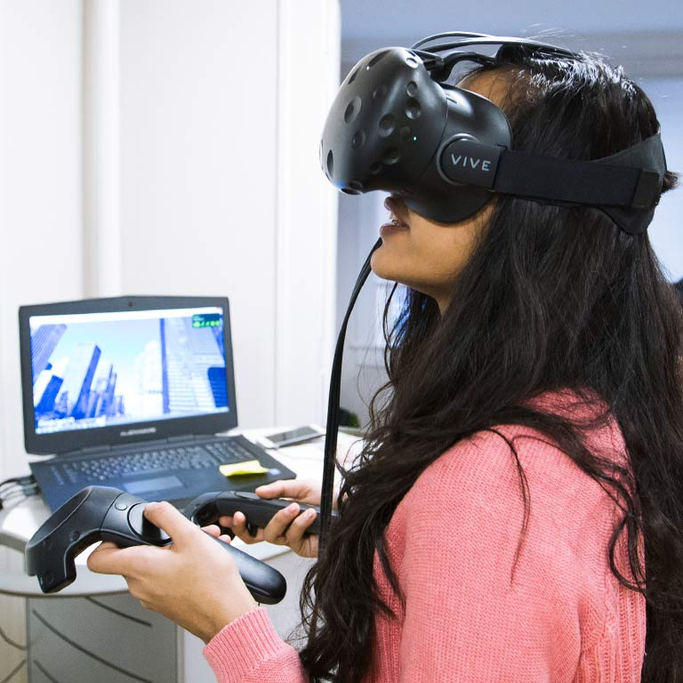 A student uses a virtual reality headset and controllers while a laptop shows what she is seeing.