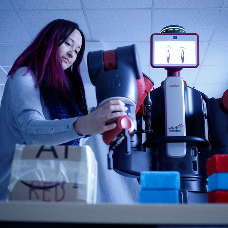 An student works with a robot for her research.