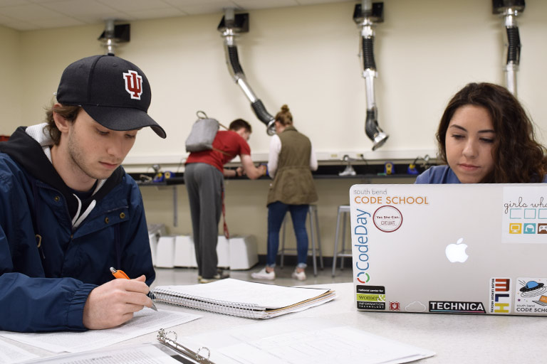 Students work on their projects at tables in a makerspace lab in Luddy Hall.