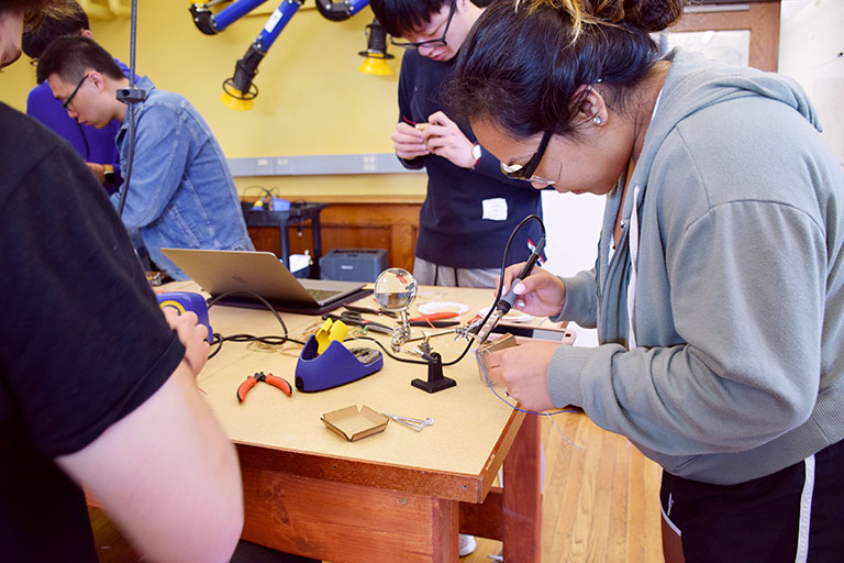Students wearing goggles work on soldering prototypes in a lab in Luddy Hall.