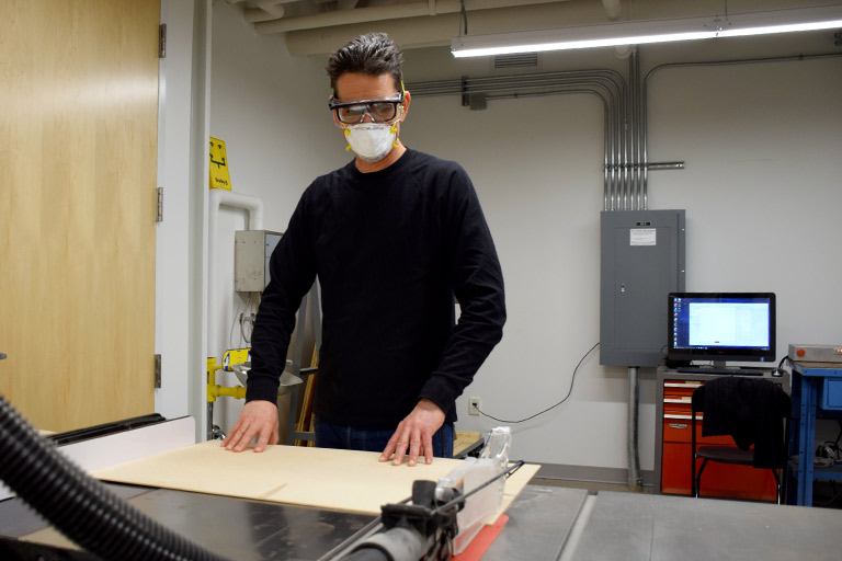 A student wearing a mask and goggles works on a prototype in a lab in Luddy Hall.