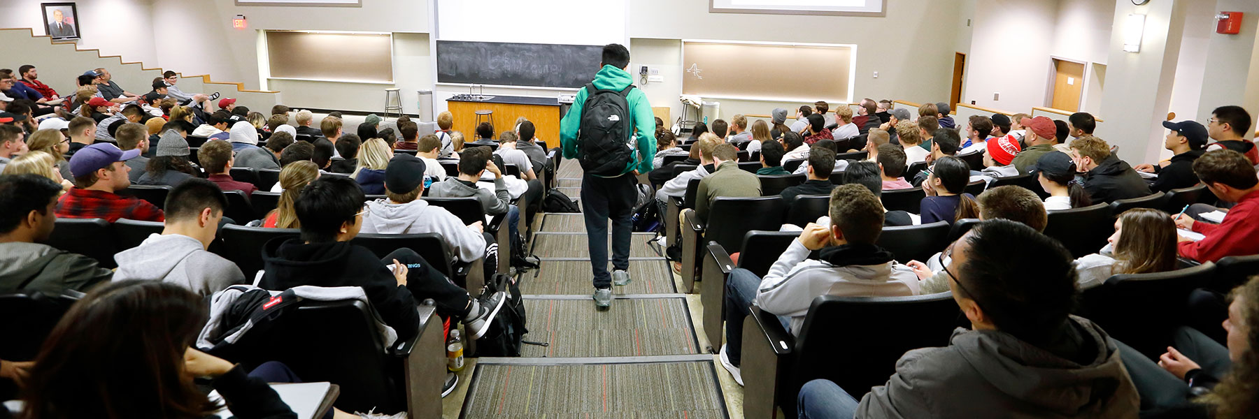 A student walks down the stairs to join his class in a large lecture hall.