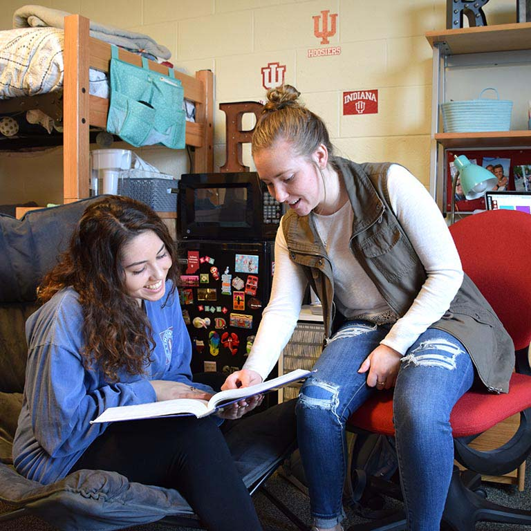 Two students who are part of the SICE LLC study a book together in their dorm room.