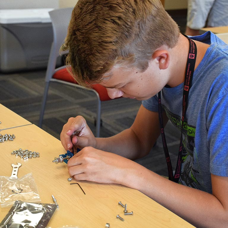 A student builds a device with tools during SICE Summer Camp.