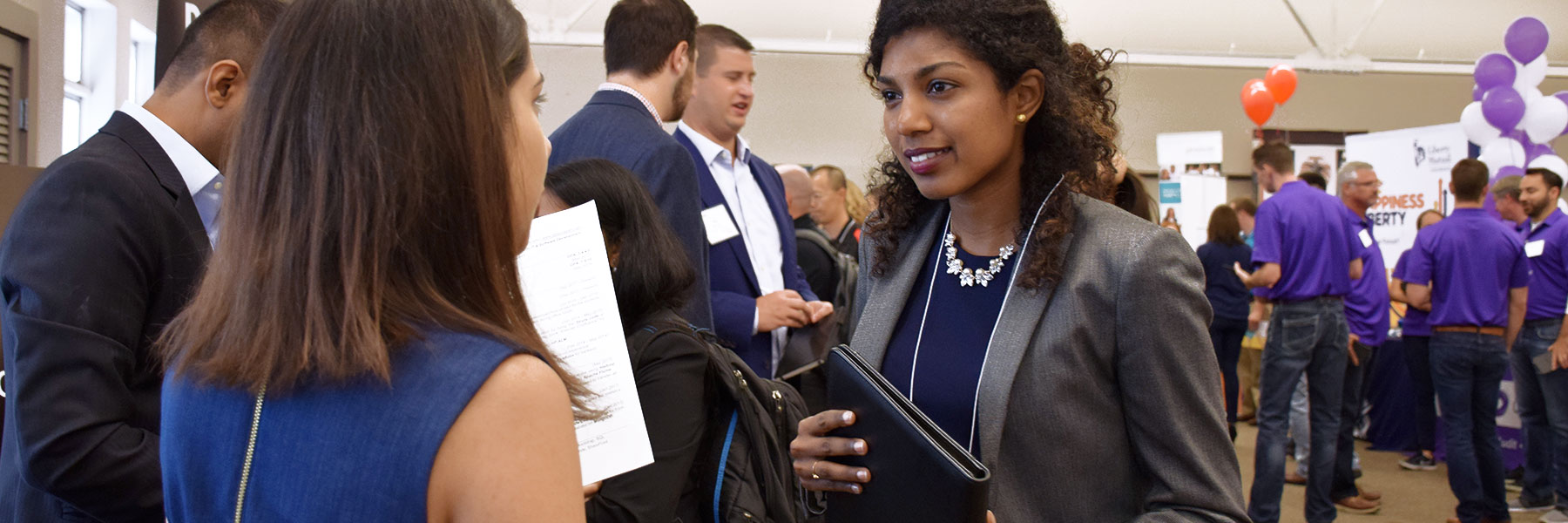 A student holds a portfolio and speaks with a representative at a career fair.