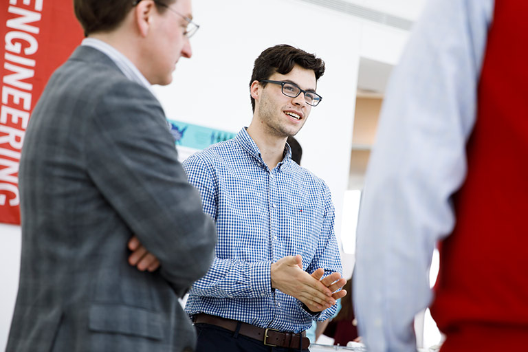 A student speaks with potential employers at a career event.