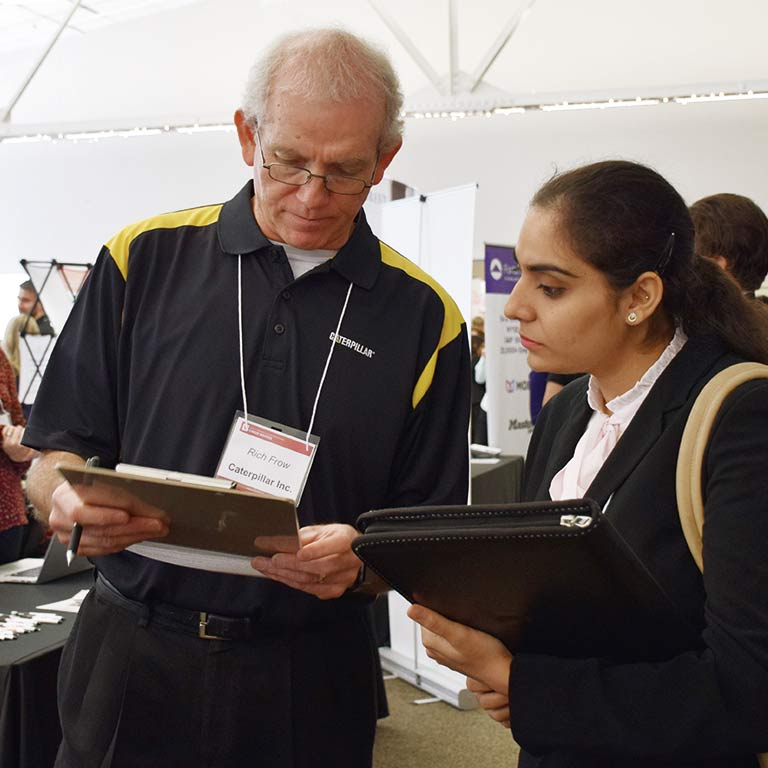 An employer looks at a form with a student at a career event.