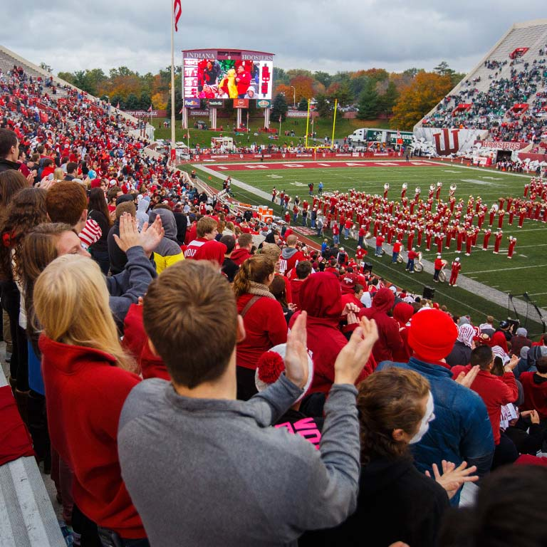 Students clap during the marching band's performance at Memorial Stadium.