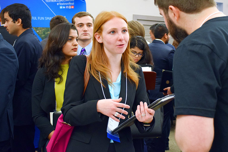 A student holds a portfolio and speaks with an employer at a career fair.
