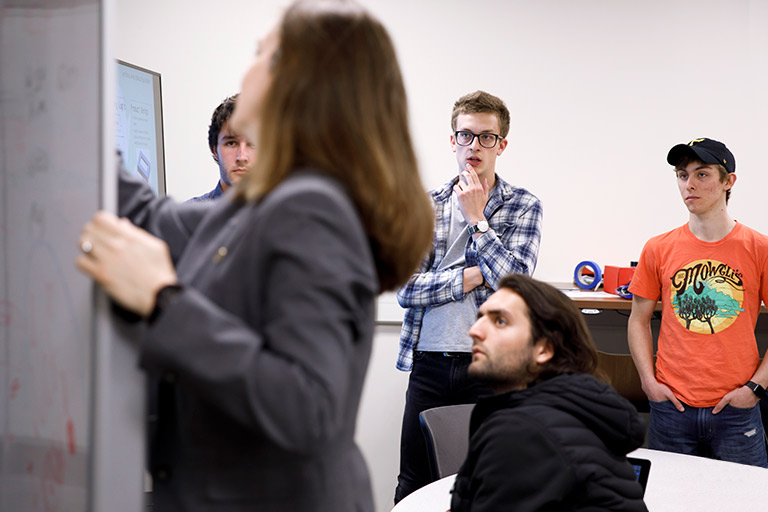 A professor writes notes on a whiteboard as a small group of students watch.