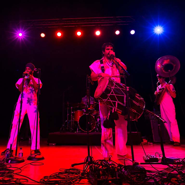 A musical group composed of drums and horns performs on a stage.
