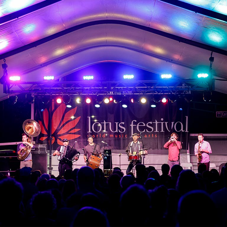 A group of musicians plays on stage at Lotus Festival in Bloomington Indiana.