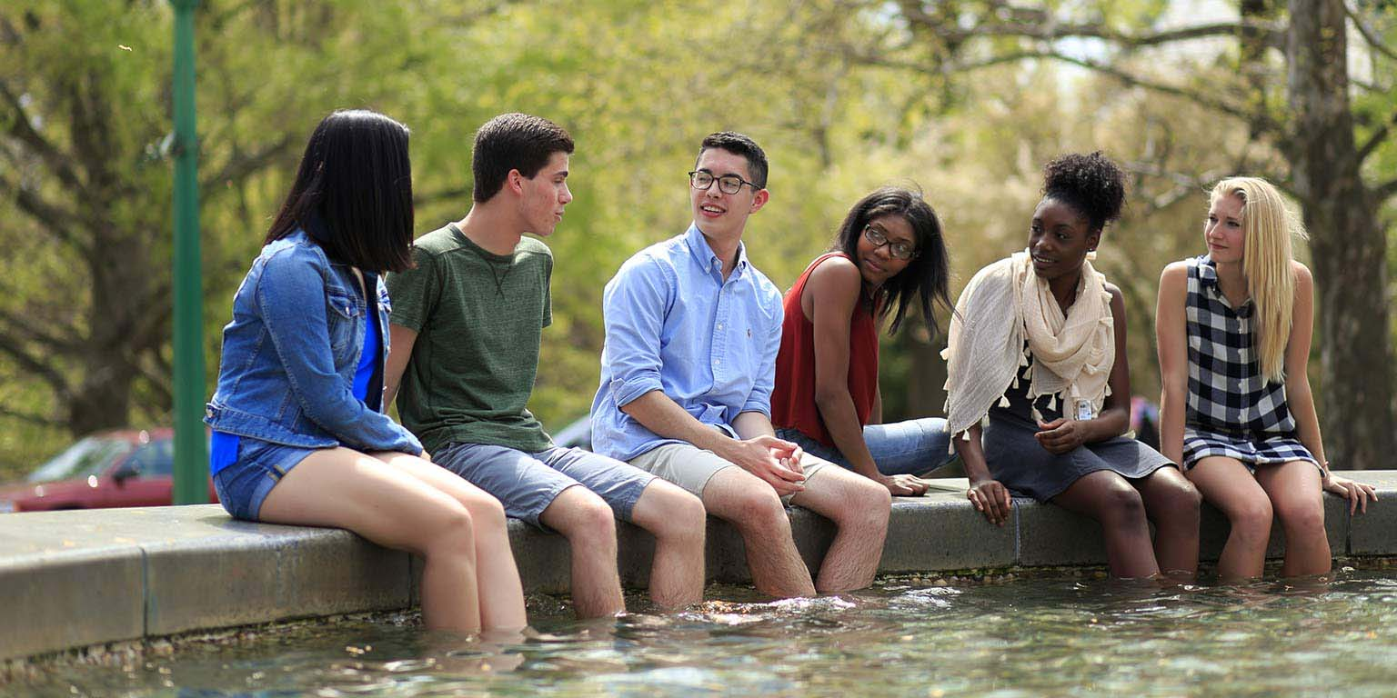 A group of students dangles their feet in the water in Showalter Fountain in Fine Arts Square.